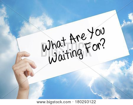 Man Hand Holding Paper With Text What Are You Waiting For?  . Sign On White Paper. Isolated On Sky B