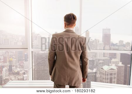 Involved in work. Professional serious businessman standing near window and mulling over his businessplan while working in the office