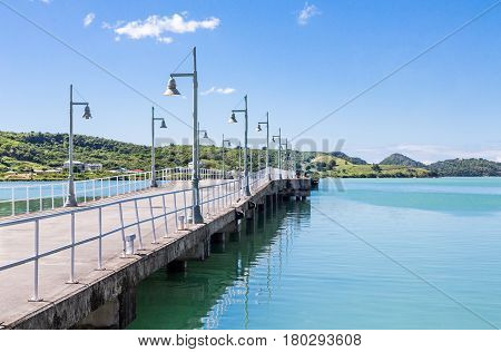 A long concrete pier with lights into the harbor on Antigua