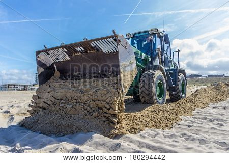 Kijkduin the Netherlands - April 6 2017: Tractor Front End Loader moving sand