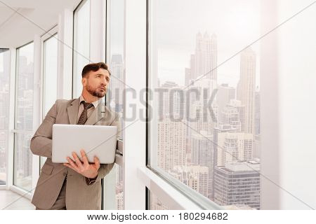 Searching for business partner. Concentrated serious businessman leaning on the office window and looking outside while holding laptop