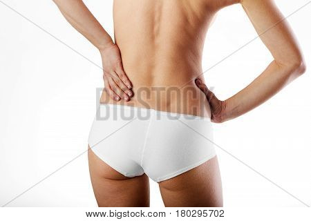 Woman with naked back rubbing her sore back. Health care concept.