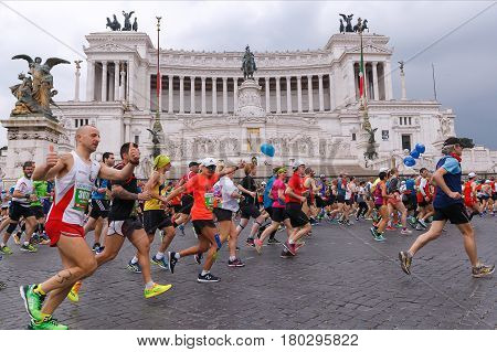 Rome Italy - April 2 2017: Athletes participating at the 23rd Rome marathon run through the street circuit passing in front of the altar of the homeland the monument to Vittorio Emanuele II king of Italy.