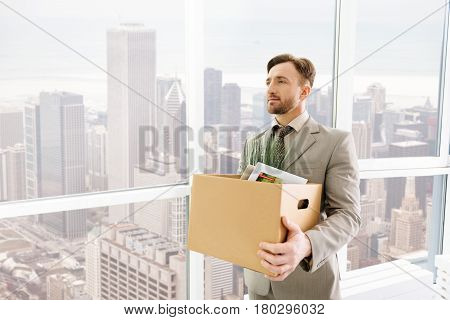 Start a new day. Pleasant serious employee holding box with belongings and standing in the office while getting ready to work
