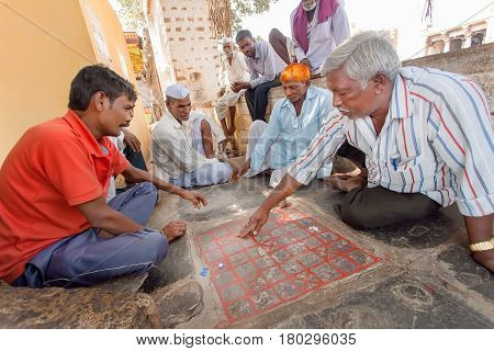 BADAMI, INDIA - FEB 8, 2017: Serious men playing traditional indian boardgame Ashta Chamma another name of ancient game Chowka Bhara on February 8, 2017. Population of Karnataka state is 62000000 people