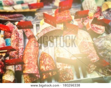 Selection of French and Italian delicatessen in butchers shop. Blurry food background with copyspace