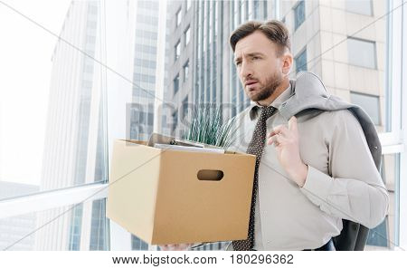 Time for change. Sad gloomy man holding his jacket on the shoulder and standing in the office while getting bed news about his dismissal