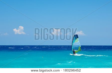 Windsurfer riding on waves in Aegean Sea. Concept of summertime, holidays and adventure.