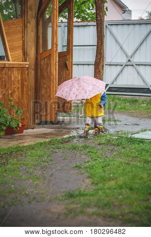 Little girl with pink umbrella playing in the rain. Kids play outdoors. Spring outdoor fun for children. Kid in raincoat and boots walking in the garden in waldorf kindergarten.