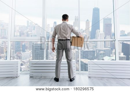 Career prospects. Rear view of pleasant employee standing near window in the office while getting promotion
