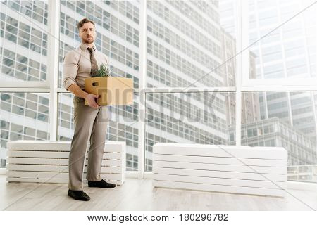 Change the surrounding. Cheerless fired man standing in the office and holding box with his belongings while feeling depressed after dismissal