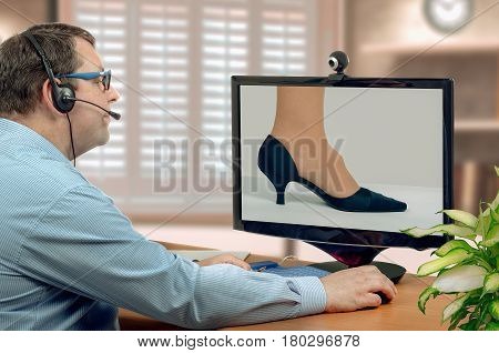 Telemedicine male orthopedist in headset looks at foot hygroma of female patient on monitor thoughtfully. Virtual doctor sees cystic tumor either by online video chat or snapshot. Horizontal mid-shot on blurry indoors background