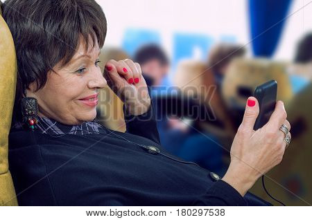 Cheerful old woman travels by bus and watching movie with mobile phone. She laying on seat looks at the screen. Medium close-up portrait on blurred bus interior background. Traveling conception