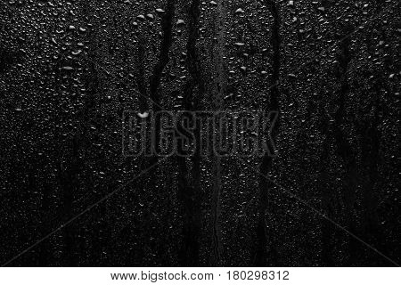 Part of series. Background photo of rain drops on dark glass different size: small medium and large horizontal view
