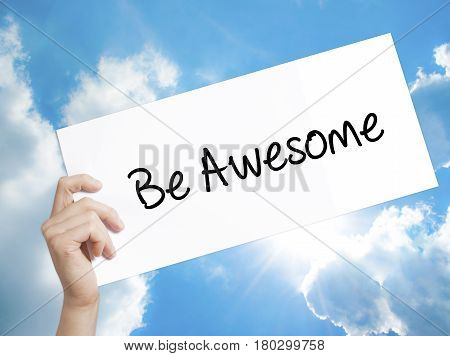Man Hand Holding Paper With Text Be Awesome . Sign On White Paper. Isolated On Sky Background