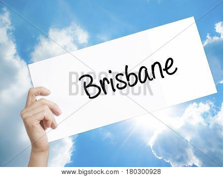 Man Hand Holding Paper With Text Brisbane  . Sign On White Paper. Isolated On Sky Background