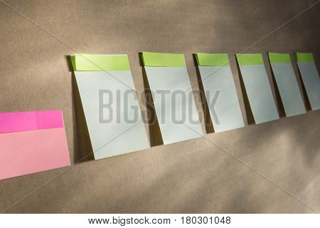Horizontal board with many white sticky notes pinned. Week is painted