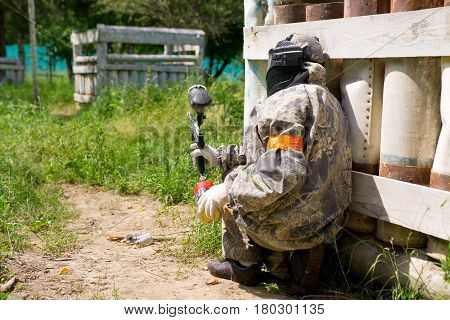 MOSCOW - JUNE 23, 2012: Paintball sport player goes to attack hides in shelter.