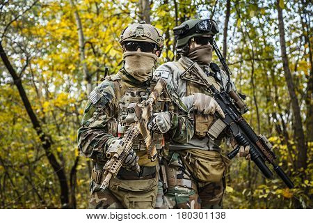 Two United states Marine Corps special operations command Marine Special Operators also known as Marsoc raiders in camouflage uniforms in the forest