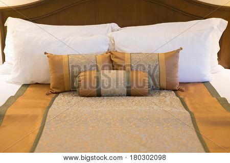 Hotel room setting with king sized bed decorated with pillows in hotel Thailand