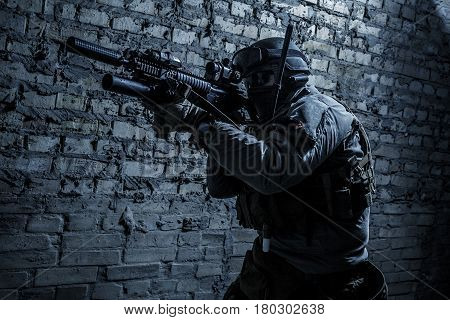 Special forces operator pointing weapon in the dark. Combat helmet, tactical radio system with folding antenna are on. Low key image