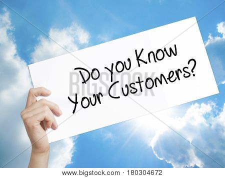 Man Hand Holding Paper With Text Do You Know Your Customers? . Sign On White Paper. Isolated On Sky