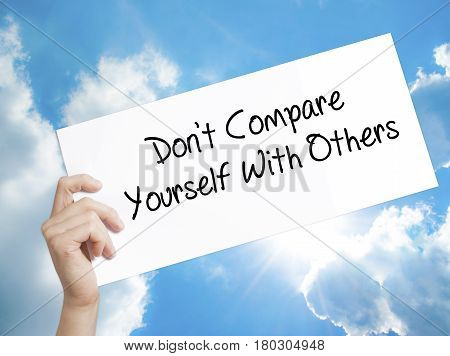 Man Hand Holding Paper With Text Don't Compare Yourself With Others . Sign On White Paper. Isolated