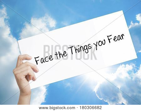 Man Hand Holding Paper With Text Face The Things You Fear . Sign On White Paper. Isolated On Sky Bac