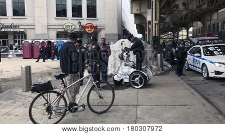 BRONX NEW YORK - MARCH 14: Man with bike speaks to police with an electric standup vehicle nearby. Taken March 14 2017 in New York.