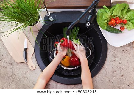 Washing vegetables to make a fresh salad - child hands scrubbing a pepper under the kitchen tap