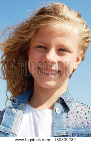 Portrait of a little girl in a jeans waistcoat on a blue sky background