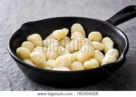 Raw gnocchi in cast iron frying pan on gray stone background.