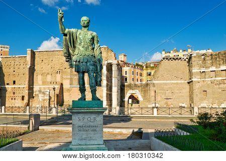 Bronze statue of the emperor Nerva against the forum of Augustus, Rome