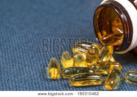Fish oil capsules with omega 3 and vitamin D in a glass bottle on blue sackcloth texture healthy diet conceptisolated on a white background.
