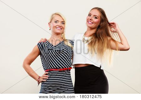 Fashionable style clothes concept. Woman wearing white top and black shirt standing next to older female with striped dress