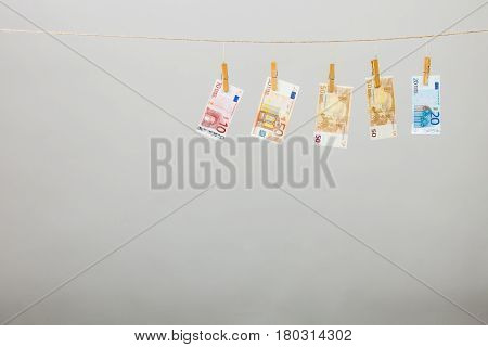 Banknotes cash money hang on laundry line on gray grey background.