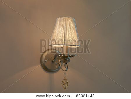 Old style switched on lamp mounted on beige wall with lampshade