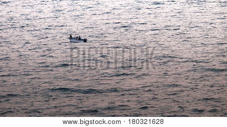 silhouette minimalist of single fishery boat float on calm sea with copy space