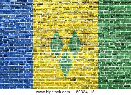 Flag of Saint Vincent and the Grenadines painted on brick wall, background texture