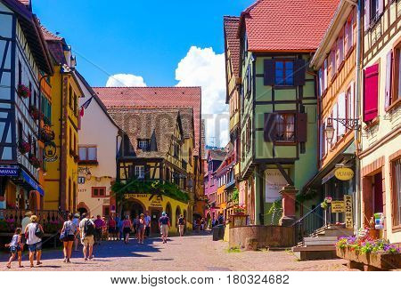 Riquewihr France-June 23 2016: Tourists are walking on the main shopping street; Rue du General de Gaulle in Riquewihr Alsace wine road
