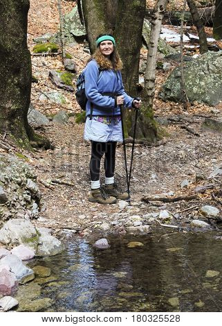 A Woman Hiker Stands Smiling by a Forest Creek