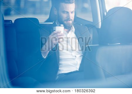 Handsome businessman sitting with coffee to go on the backseat of the car. View through the window