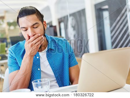 Tired programmer working overtime with computer at office