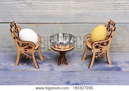 Easter Egg In Wooden Chairs At Table With Metallic Bowl