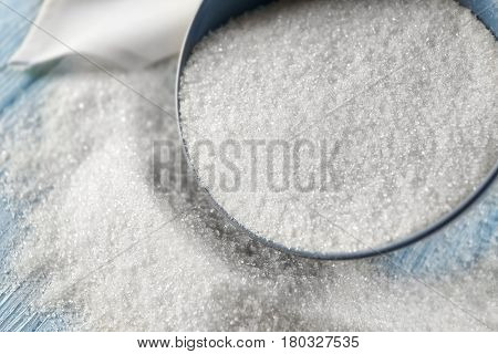 White granulated sugar scattered from bowl on wooden background