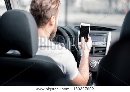 Man using a smart phone sitting on the front seat of the car. Back view focused on the phone with empty screen