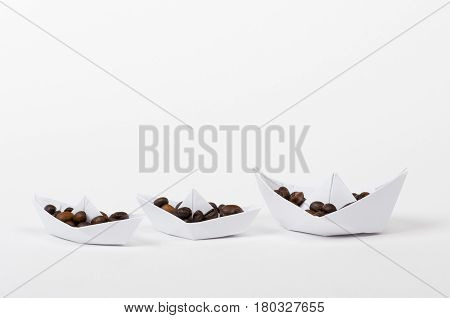 three white paper boats loaded with coffee beans, white isolated closeup