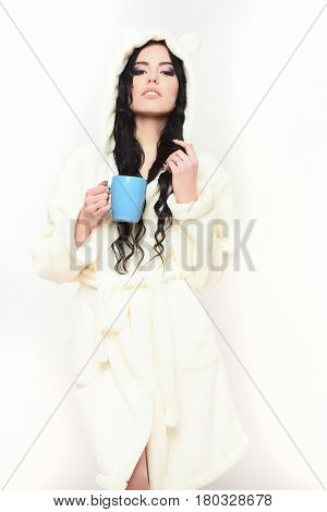 pretty serious cute sexy girl or beautiful woman with fashion makeup and curly long hair posing in beige velour bathrobe with cup isolated on white background