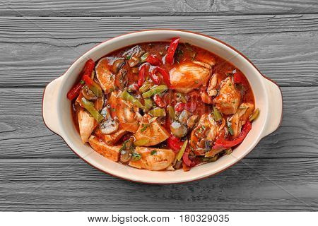 Delicious chicken cacciatore in baking dish on kitchen table