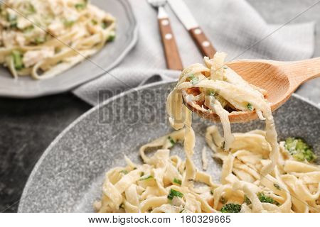 Spoon with tasty chicken Alfredo over frying pan